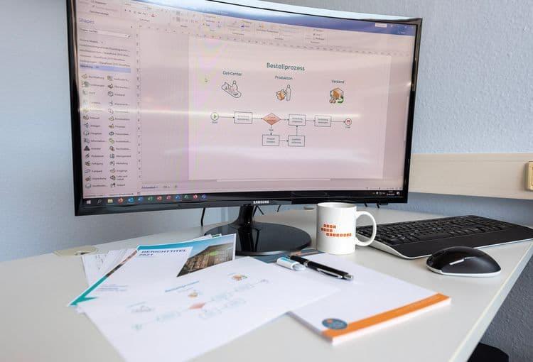 Bildschirm mit Visio-Übung und ausgedruckten Visio-Lernunterlagen