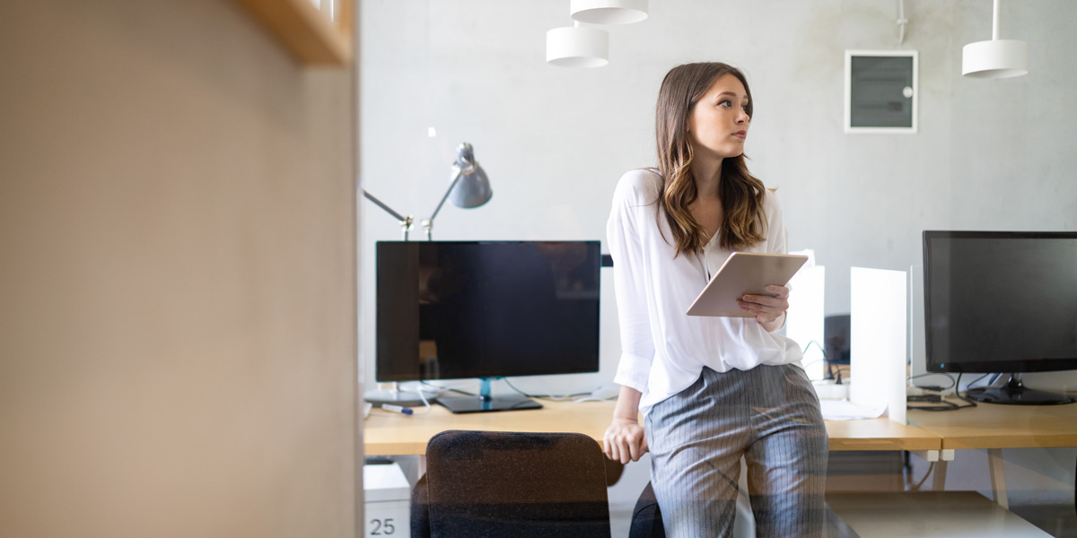 A data analyst leaning back against a desk, holding an iPad and looking off into the distance