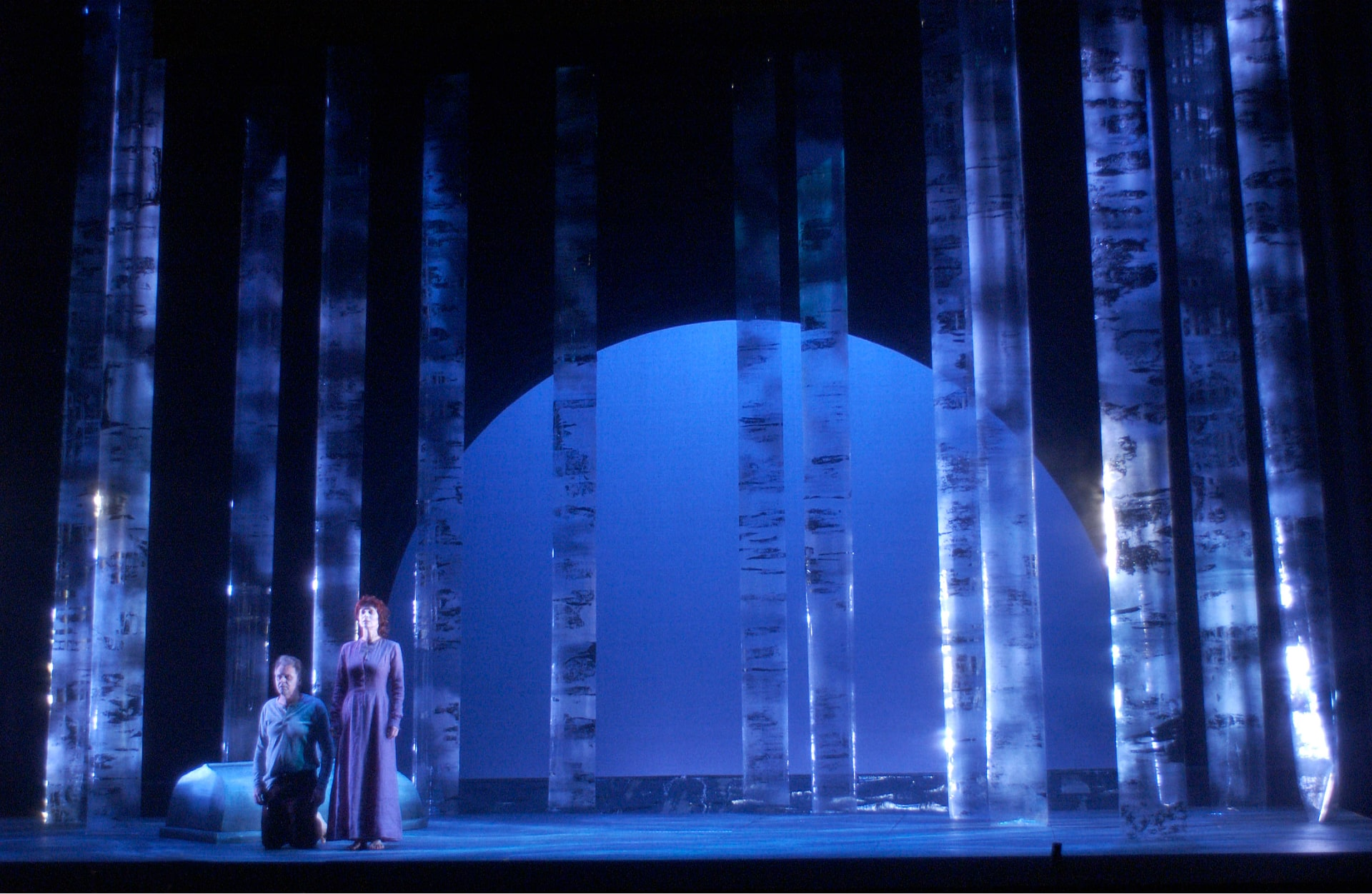 Woman in grey dress stands beside kneeling man before plexiglass forest and pale blue sunrise.