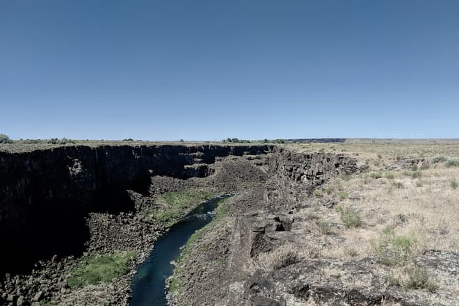A river cuts a deep, sheer canyon through the basalt underlying otherwise empty desert scrubland.