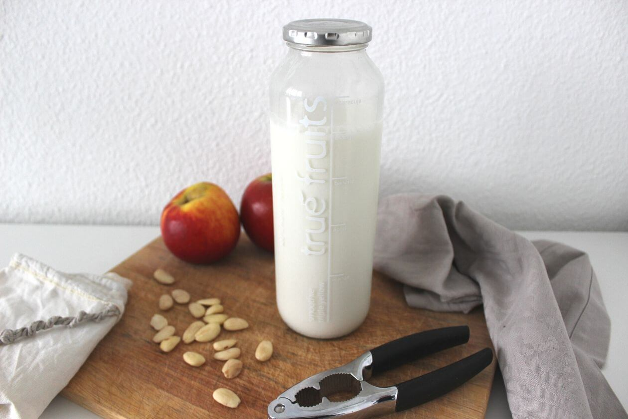 Ein Flasche Mandelmilch auf einem Brett, einzelne Mandeln verstreut im Vordergrund, im Hintergund ein paar Äpfel