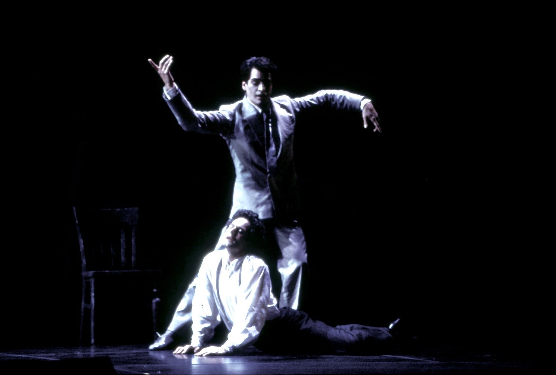 Dancer in white shirt arches at feet of dancer in white suit with arms outstretched.