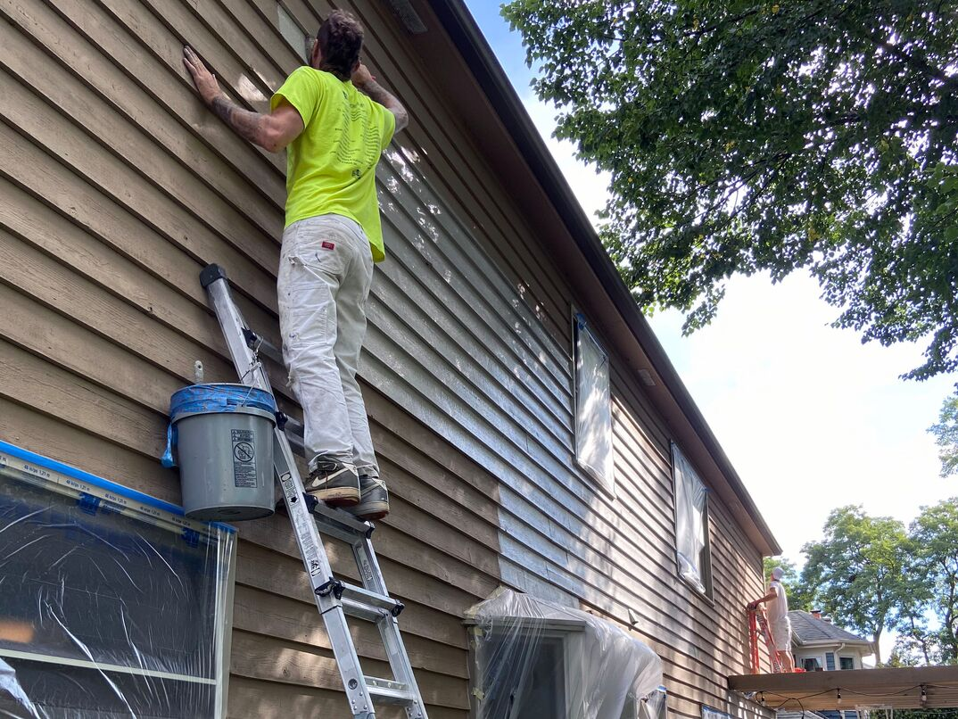 man in yellow shirt standing tall on a ladder painting a house