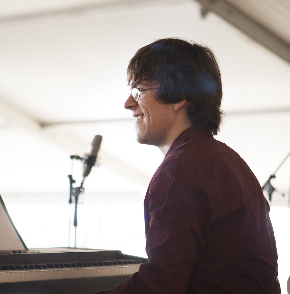 Jake Butineau sitting in front of a keyboard and smiling while performing on stage.