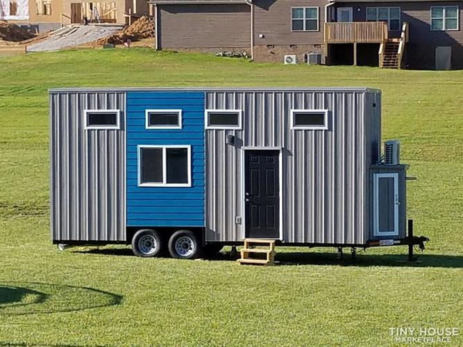 External photo of the Jefferson-based tiny home on wheels, with 5 windows and a solid front door.