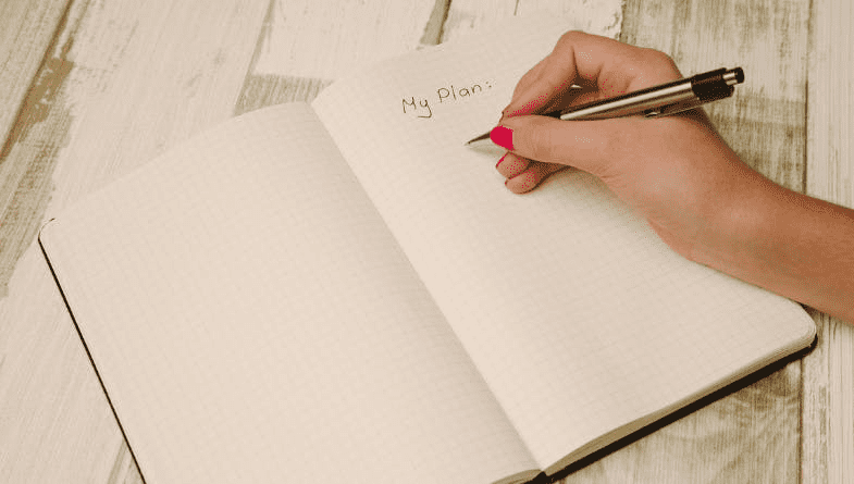 Person writes in notebook with pen and red nail polish to create beginners guide to key performance indicators for businesses for a business owner (KPI)