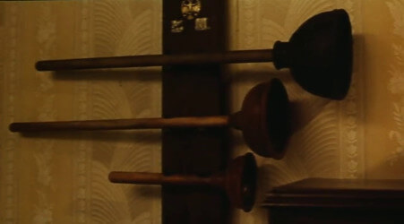 A shot from the Super Mario Bros. movie, showing a series of plungers hung on a wall as trophies