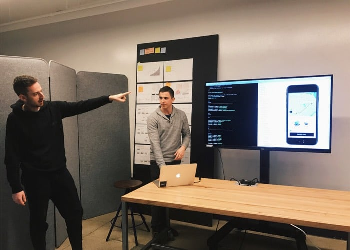 Bradley (right) and a coworker present a prototype during an internal design review.