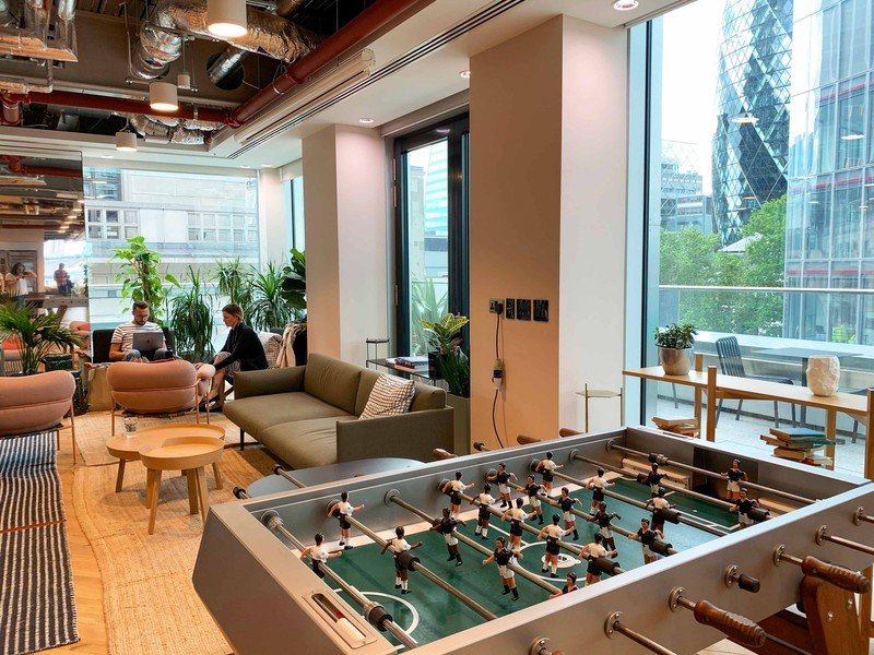 Employees work in a break room with a foosball table, comfy couches, and large windows looking out on a business district