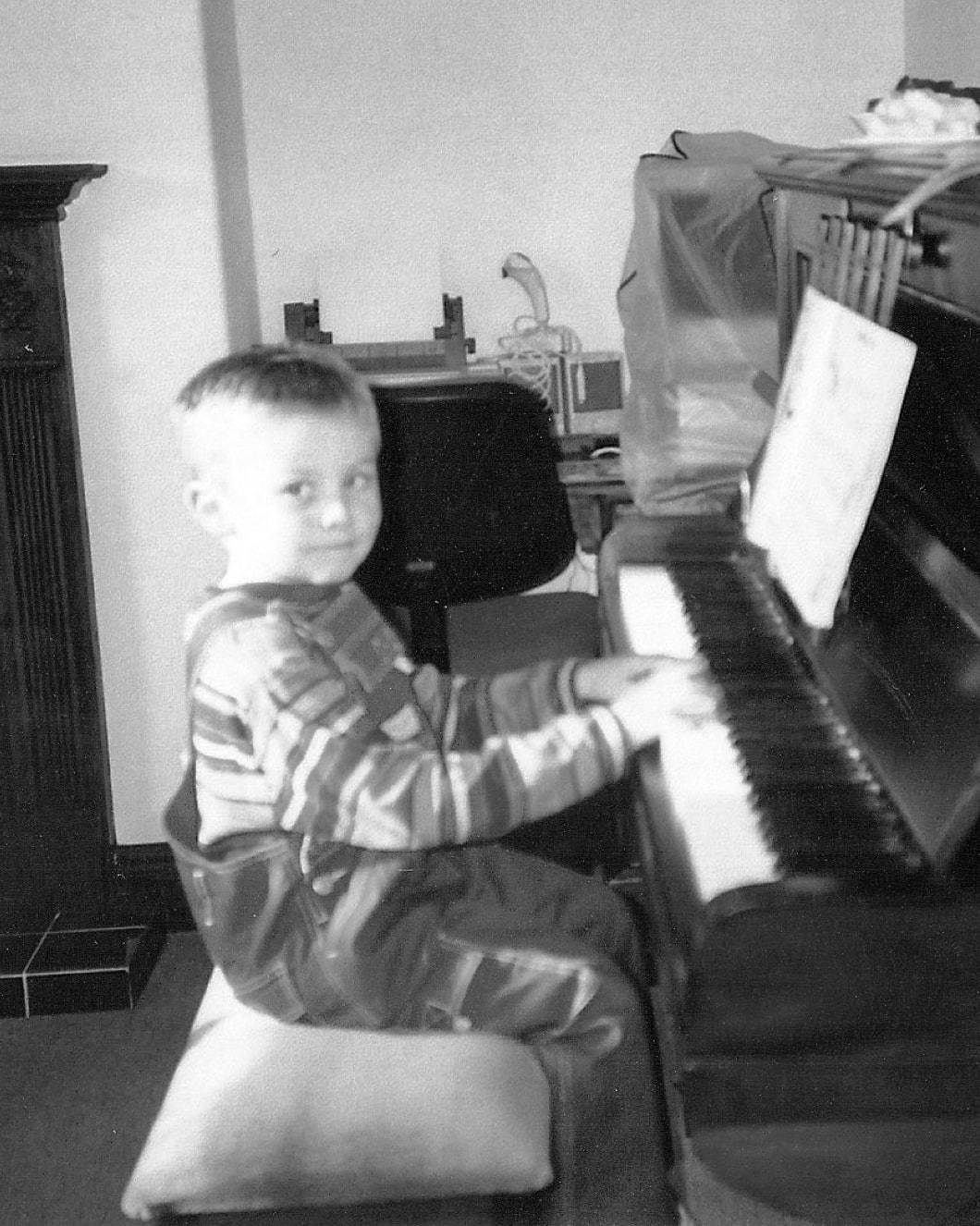 Jack Watkins as a young child playing the piano, in black and white