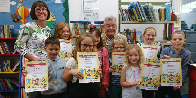 Children at Needham Market Library receive their Summer Reading Challenge certificates and medals from Deputy Mayor Steve Phillips and library manager Donna Grand.