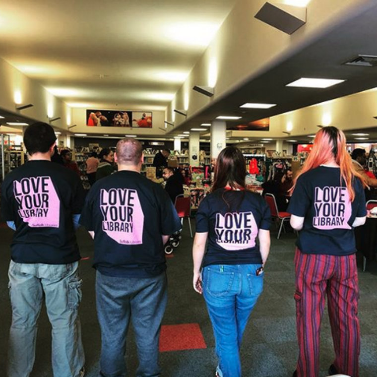 Four people in Ipswich County Library with their backs turned to the camera, wearing t-shirts reading 'Love Your Library'