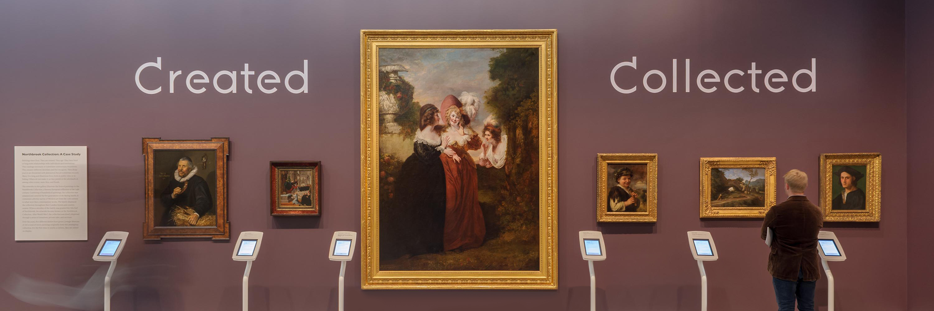 Gallery installation view featuring six paintings in thick gilded gold frames. Each painting is accompanied by an iPad. The center painting is nearly life-size and bracketed on either side by the words Created and Collected.