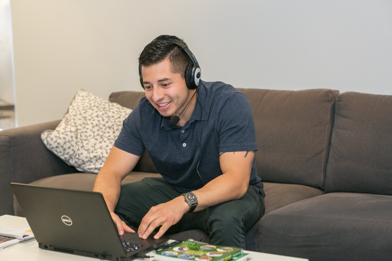 Guild Education employee working on a computer with a headset