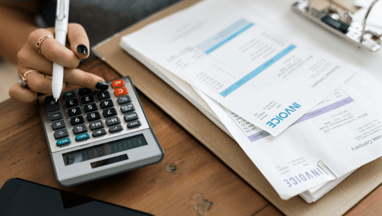 Calculator and reports, paper, notes on wooden desk to do accounting, bookkeeping, as client business owner from accountant with Futrli #Accountancy