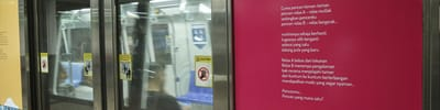 A photo of an MRT door, with a Poetry on Platforms poetry sticker on it.