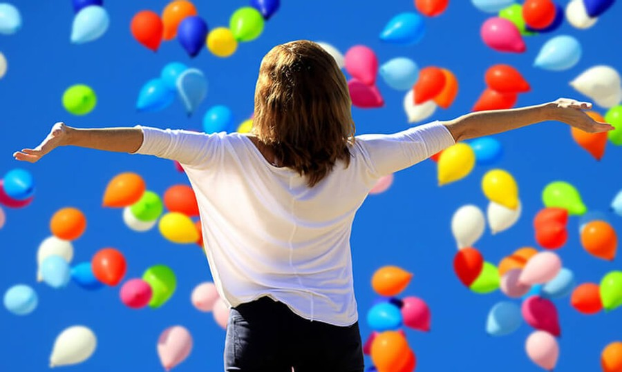 Lady happy with colourful balloons in the sky
