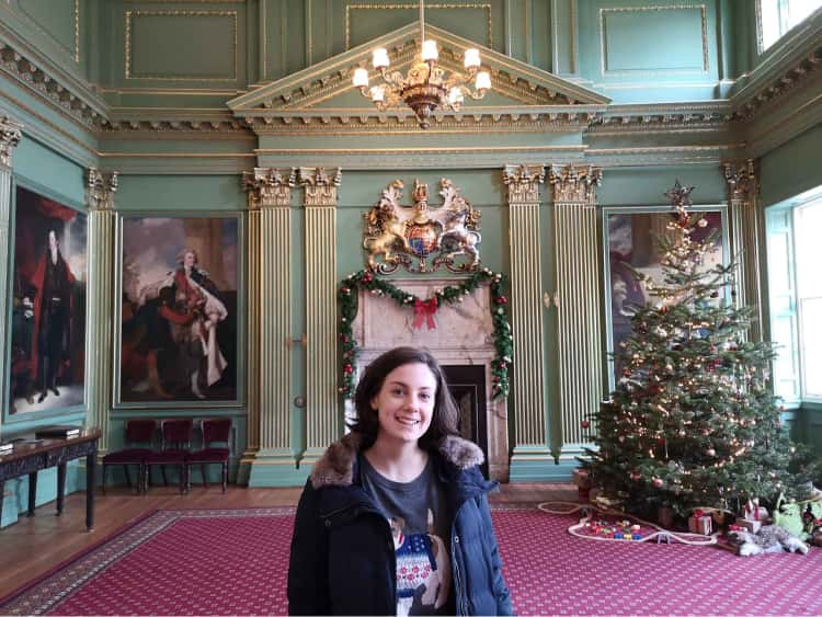 Naomi in the foreground, with a christmas tree, festive decorations amongst the traditional portraits and historic green walls of the Mansion House in York.