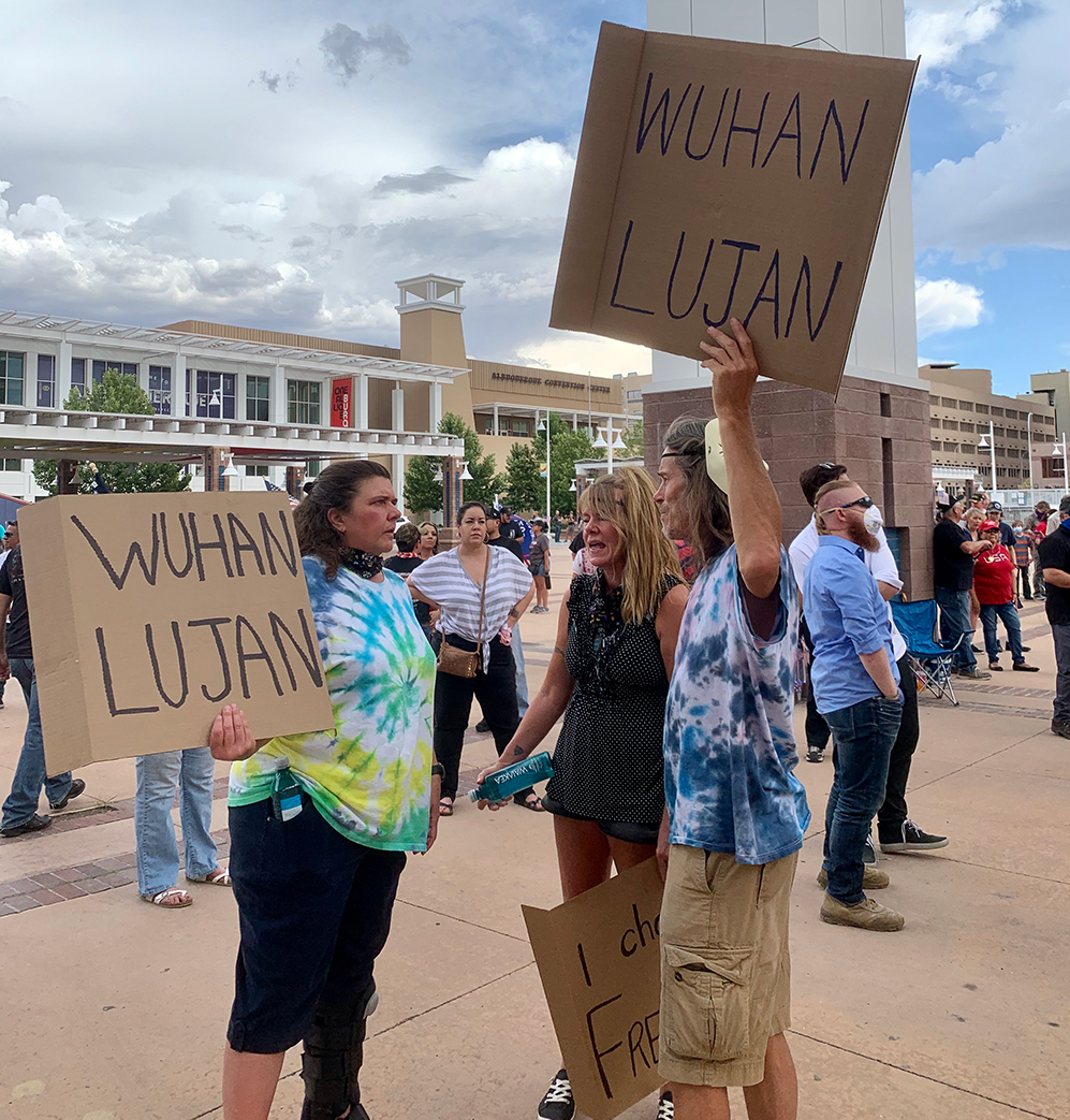 Anti-quarantine protesters carrying signs with the racist phrase 'Wuhan Lujan,' referencing New Mexico Governor Michelle Lujan Grisham. Photo by Bella Davis.