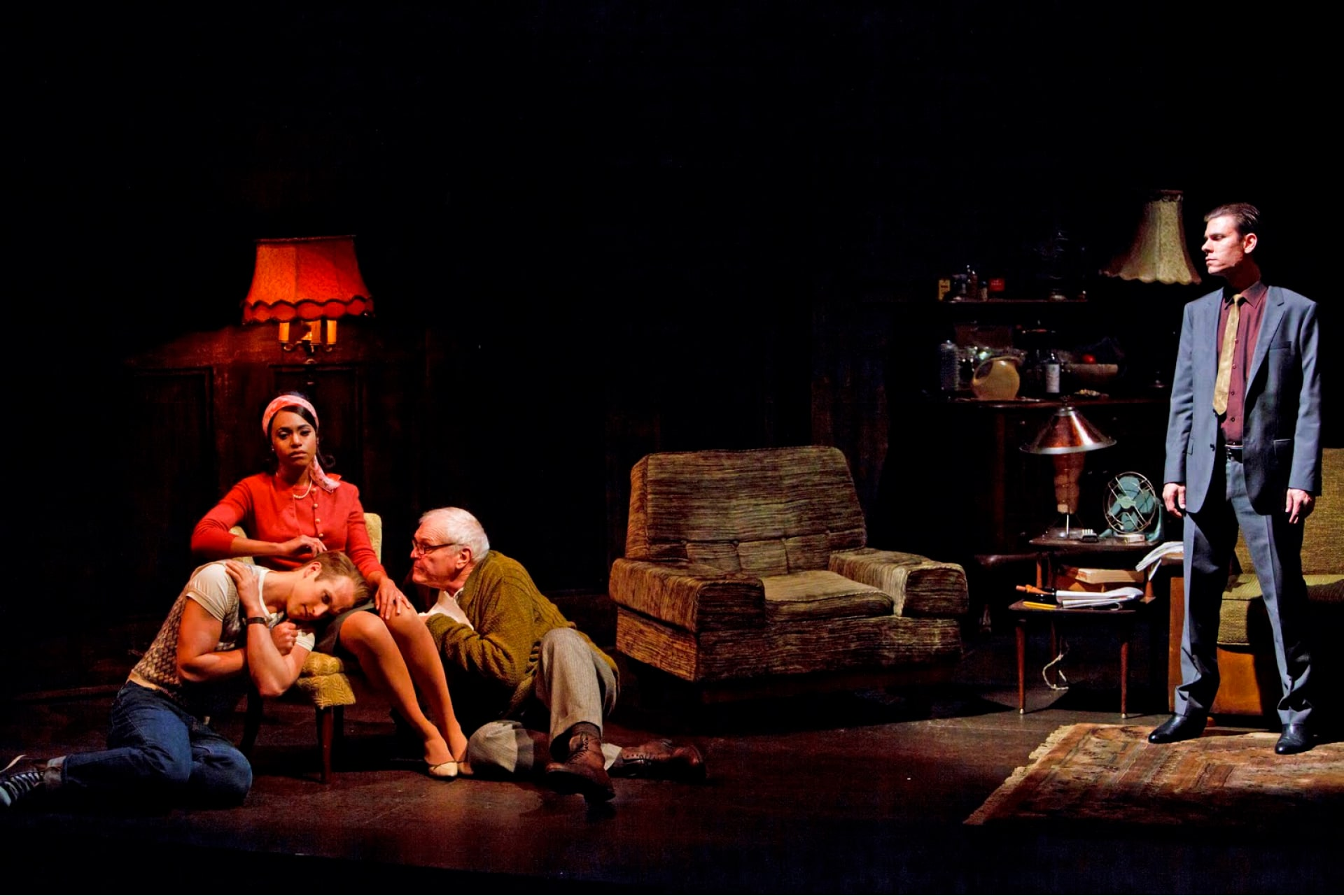 Woman sit in living room with two men crouched beside, watched by standing man