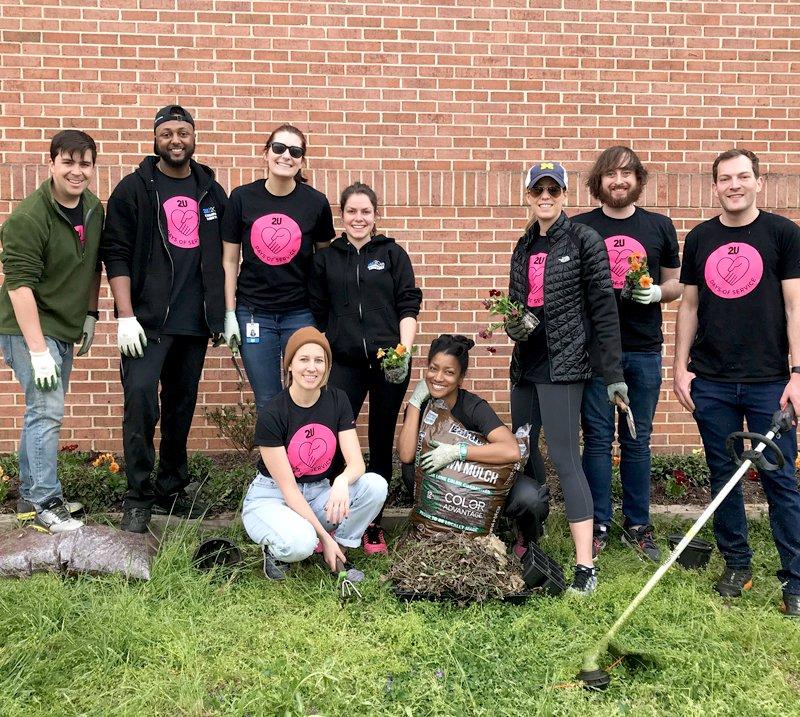 2U volunteers gardening at a community event.