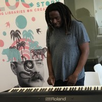 Songwriter, musician and composer Aga Serugo-Lugo playing the keyboard at Ipswich County Library