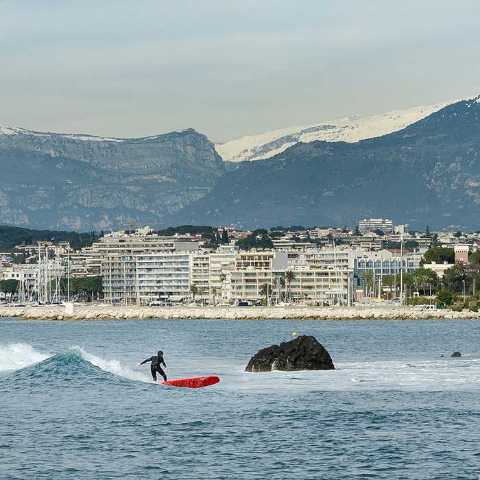Surfing in Golfe Juan, overlooked by the Parc naturel régional des Préalpes d'Azur, France