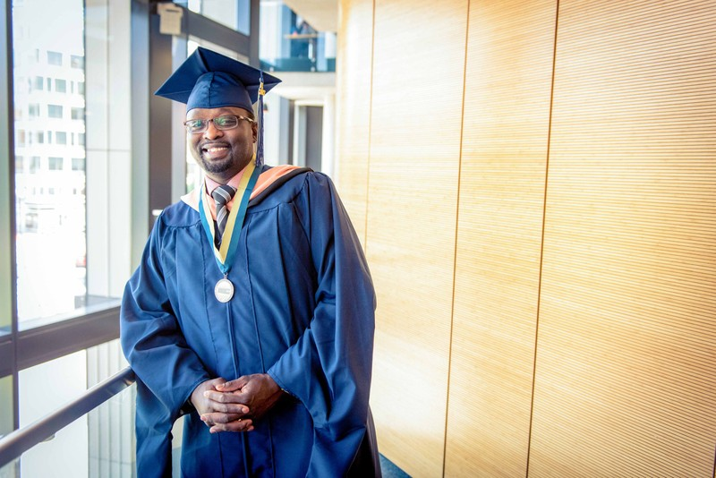 A smiling George Washington University graduate in his cap and gown with his hands folded