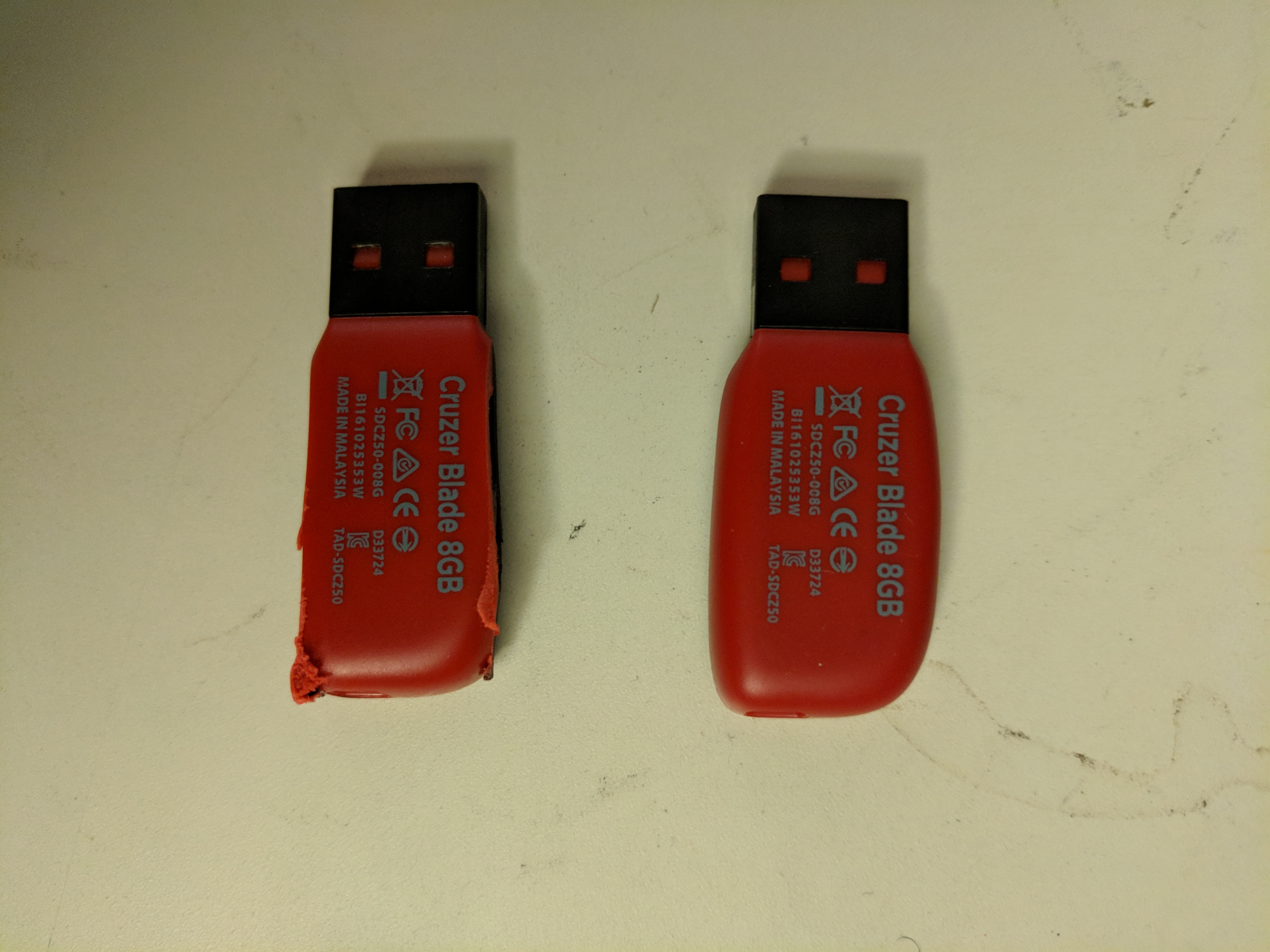 Two Sandisk Cruzer Blade 8GB USB thumb drives side by side.  The one on the left has had the case ground down to make it narrower.