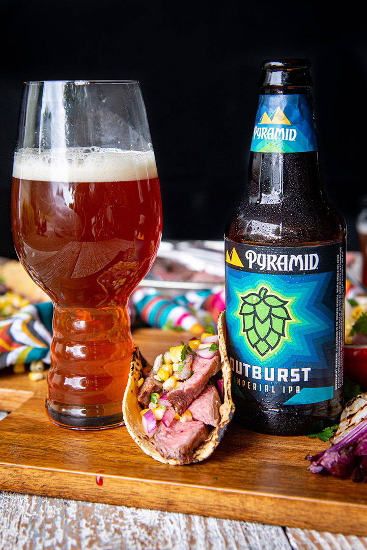 Outburst IPA Flank Steak Taco between a bottle and pint of Outburst IPA