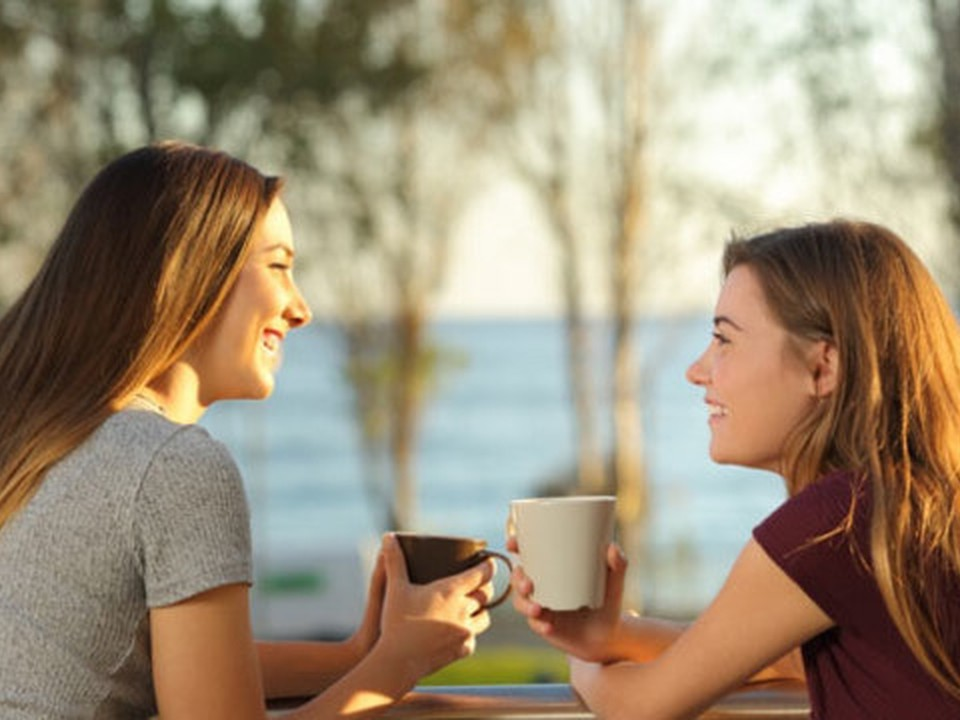 Two young women seated outdoor holding a cup and smiling at each other