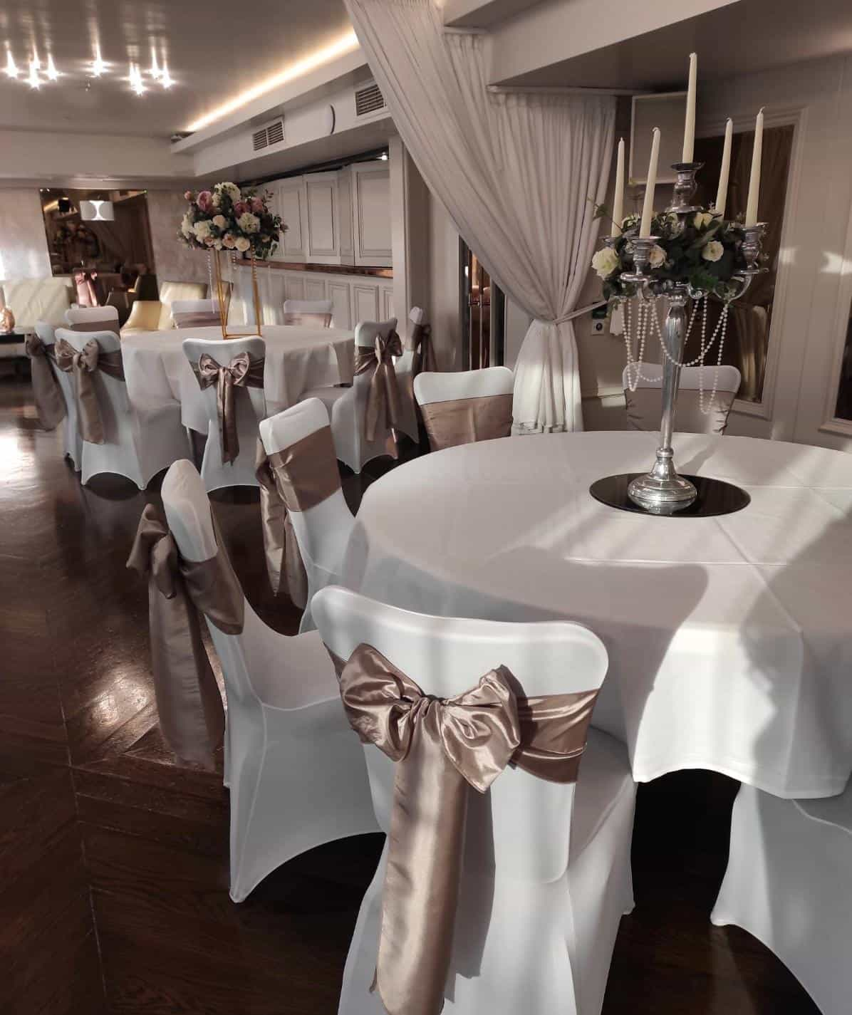 Wedding breakfast setting with white chair, table and drapes setting. Great large candleabra centrepieces and golden taffeta sash bows on chairs