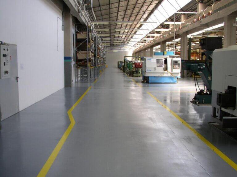 Corsie di transito delimitate da segnaletica orizzontale integrata nella superficie in resina.