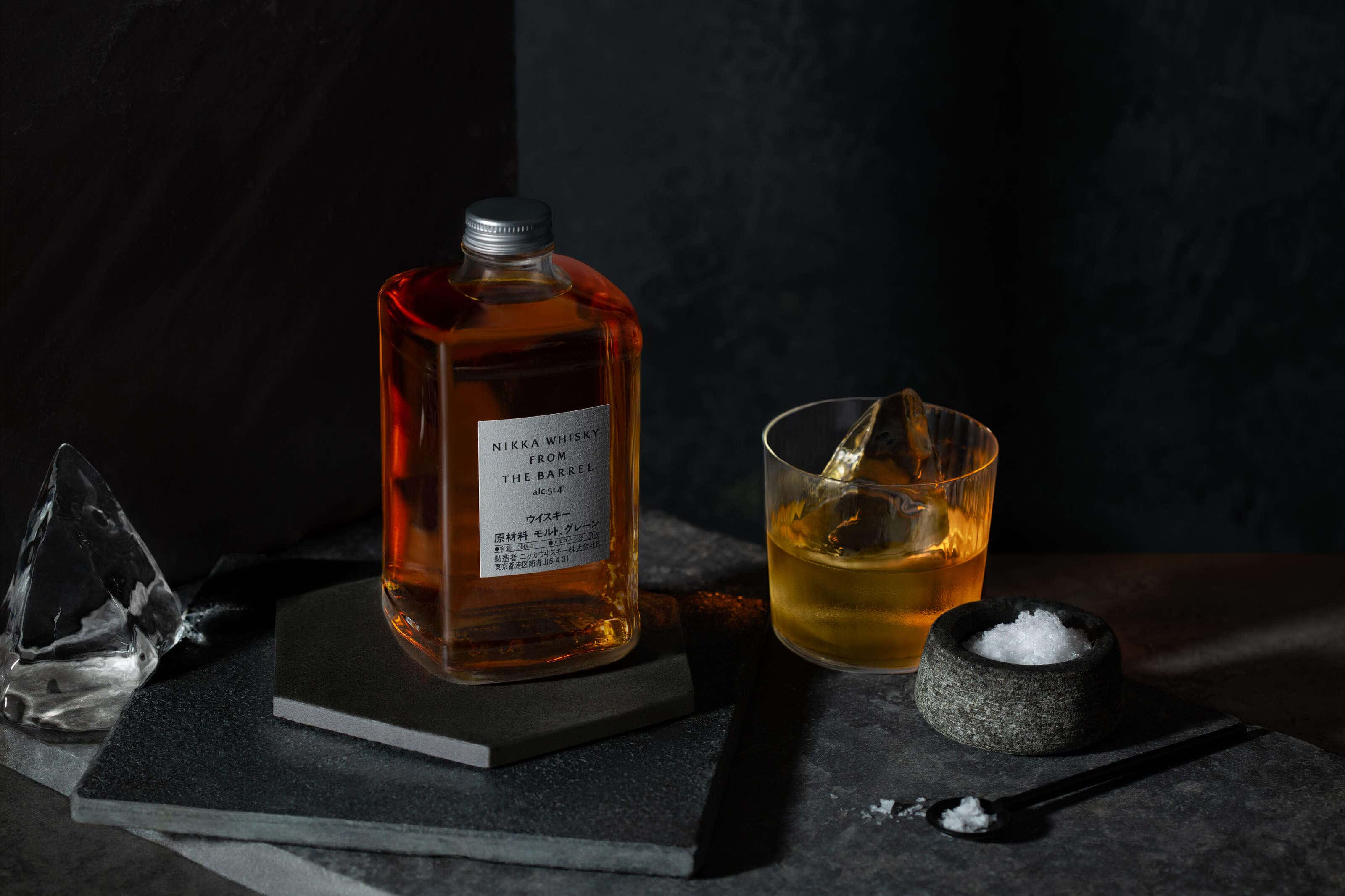 Nikka whisky in a bottle with a glass next to it with large pieces of ice
