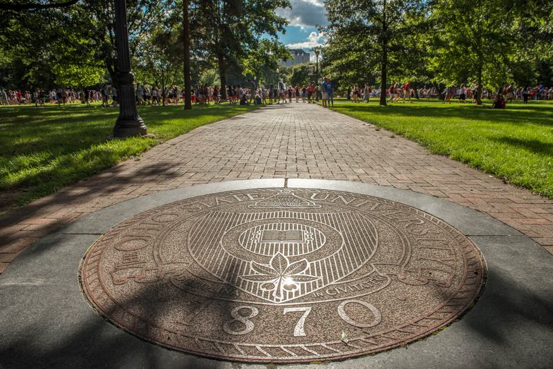 Students behind the seal on the campus of The Ohio State University