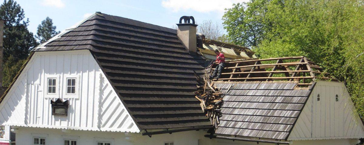 dark shingle roof undergoing repair