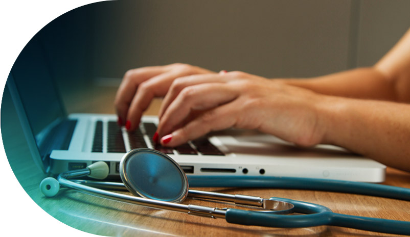 Hands typing on keyboard, next to stethoscope on desk
