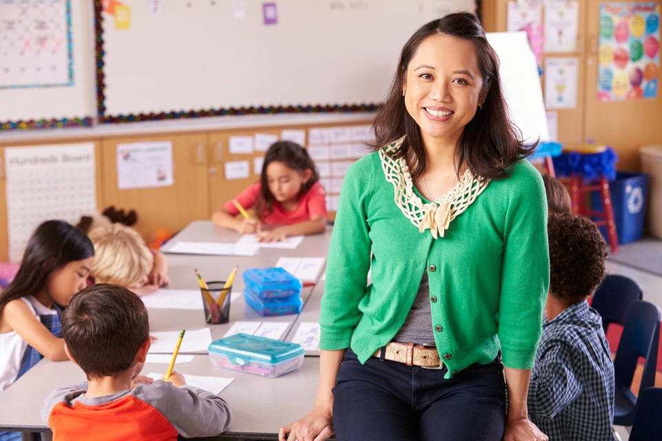 A woman smiling. Besides her we can see a children's classroom. There are some children drawing seated at a desk