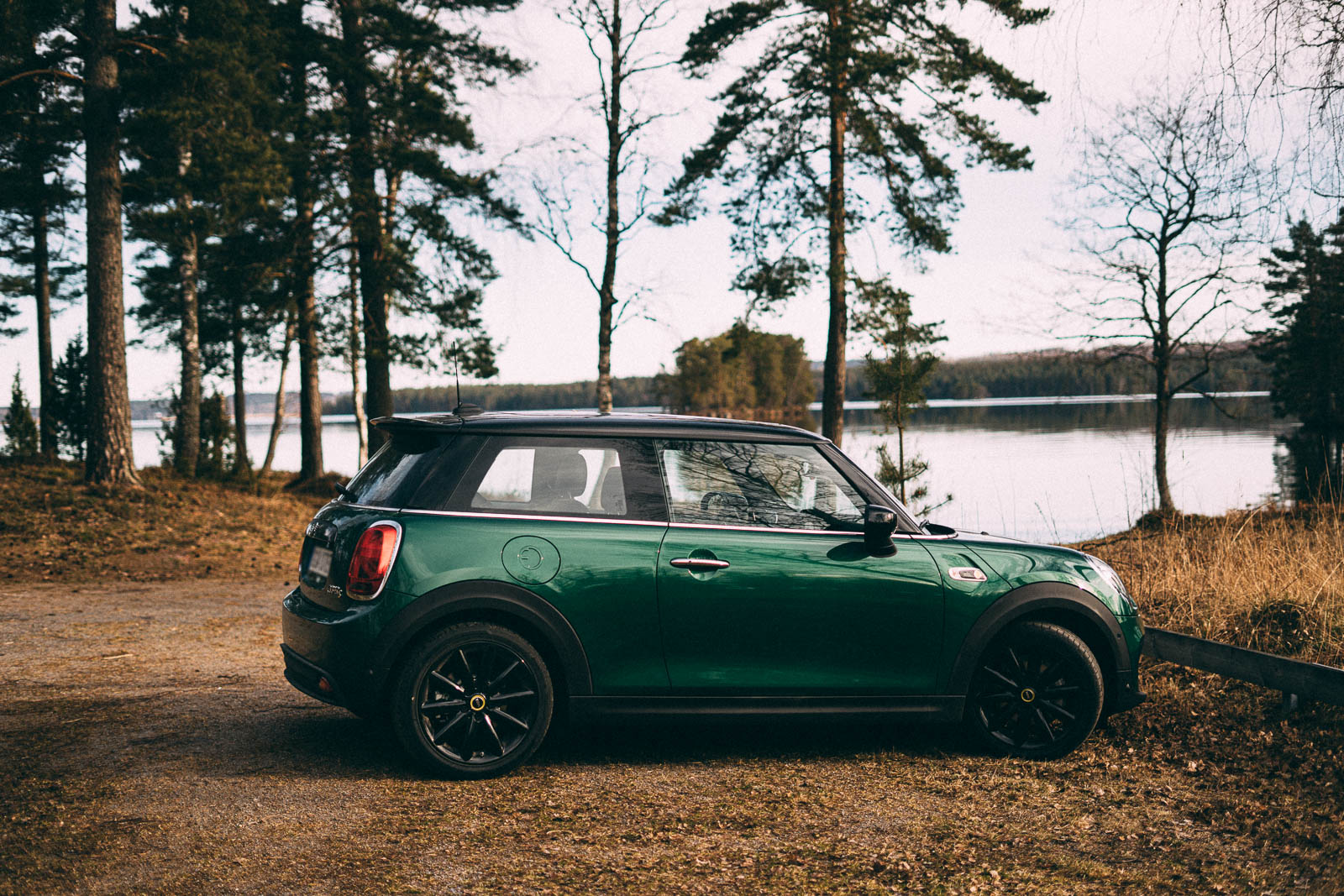 The profile of a green, three-door car. It stands parked outdoors; there's a lake in the background, and it looks like autumn.