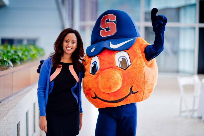 Syracuse University mascot, Otto the Orange, posing with a smiling student