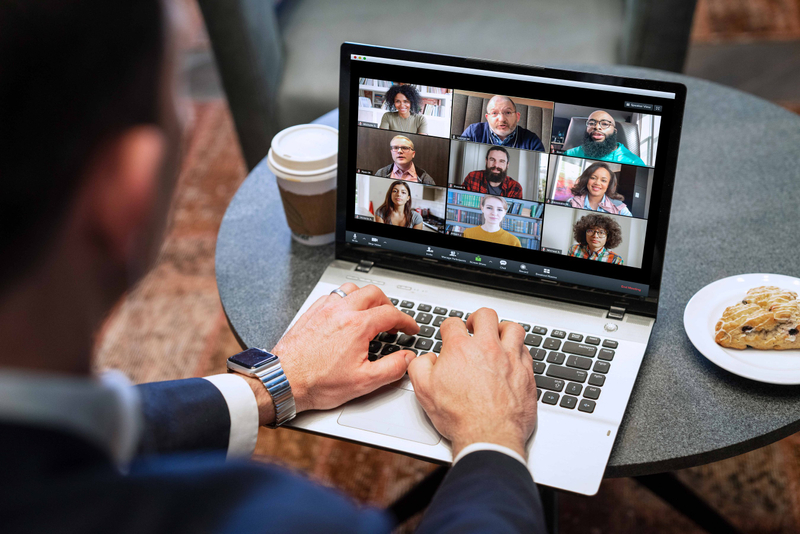 A man dials into a video chat with colleagues on his laptop while having coffee and a scone