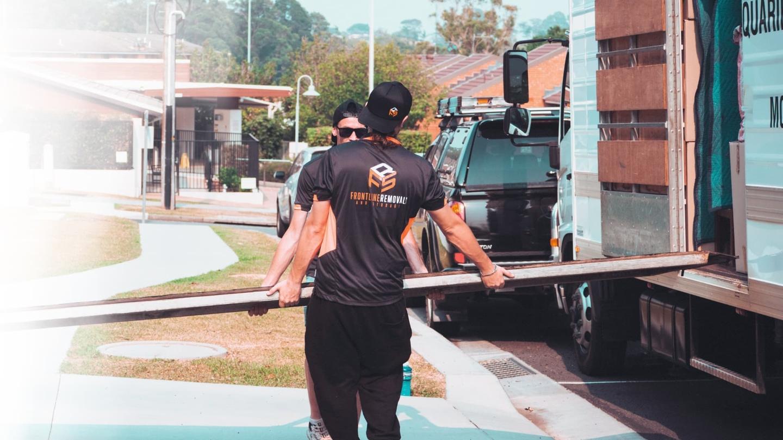 Frontline removalist crew loading materials in trailer truck