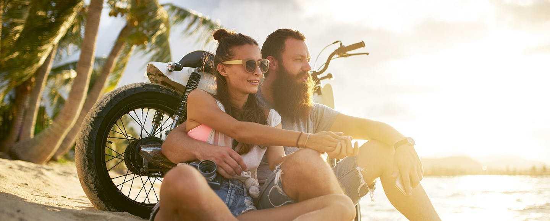 Ein junges Paar mit Motorrad am Strand - Altersvorsorge Möglichkeiten - was habe ich für Optionen und worauf muss ich achten