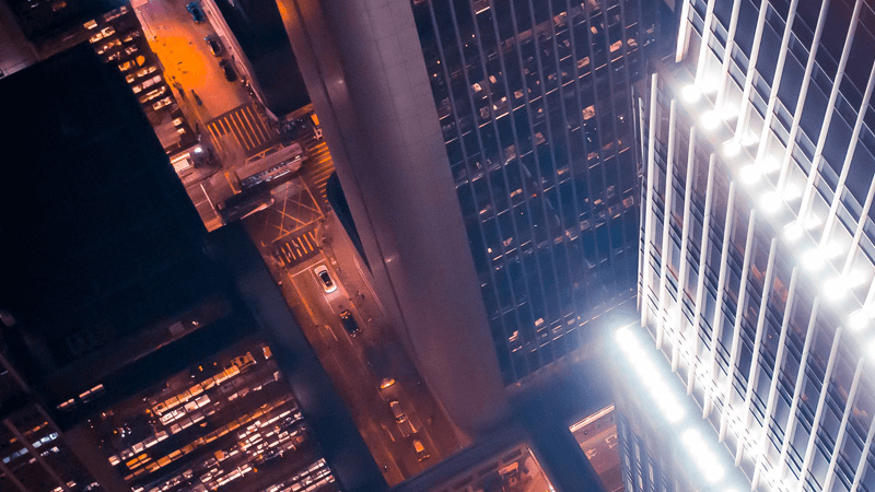 An aerial photo of illuminated, downtown office buildings and roadways at night
