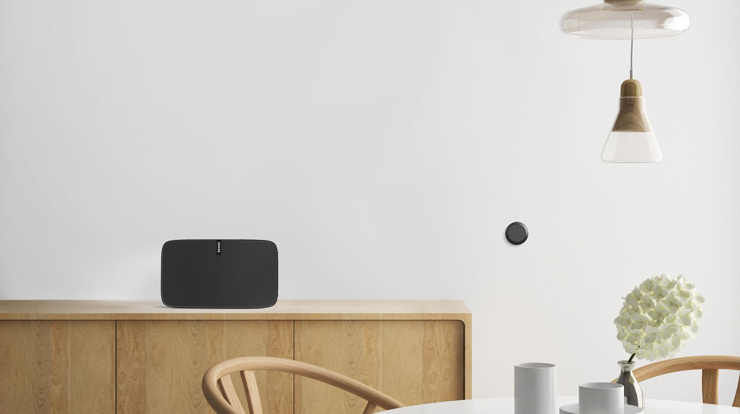 Nuimo black item on a white stylish table with Sonos speaker in the background