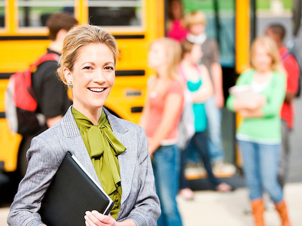 A woman smiling. Besides her we can see a school bus