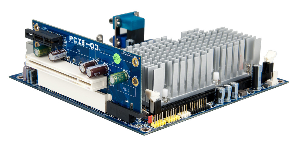 Photo of a small motherboard with a 2-slot PCIe riser card plugged in