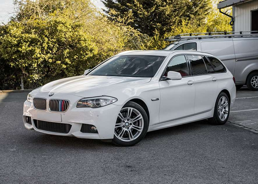 White BMW 5 series with tinted windows