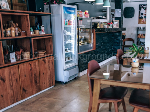 Informal Cafe Virtual Background for Zoom interior with wooden tables and tall refrigerator