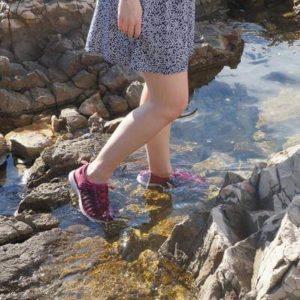 legs of woman walking on water and wearing keen uneek travel sandals